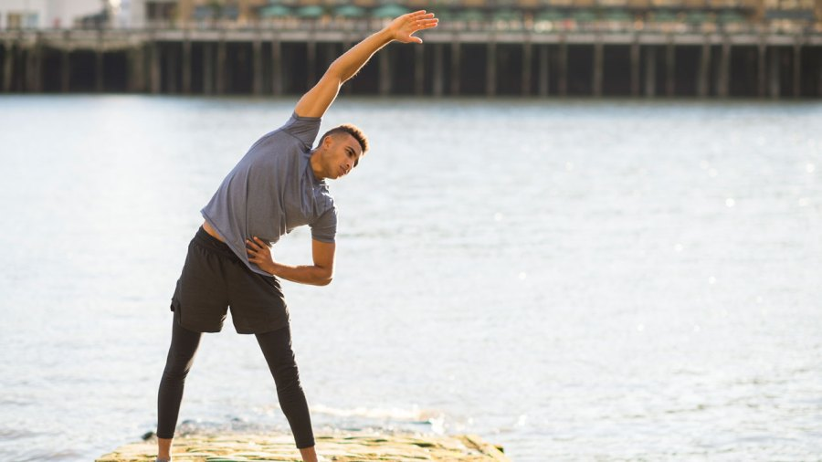 Man performing standing side stretch