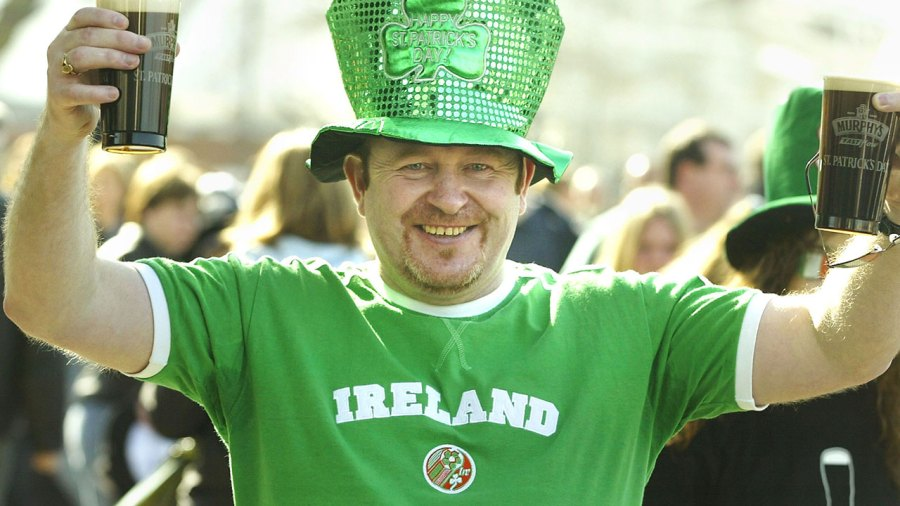 A man celebrating St. Patrick's day with beer.