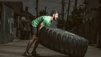Man flipping monster tire for strength training workout