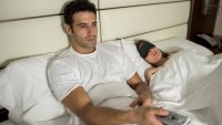 Man Watching TV in Bed Holding Remote