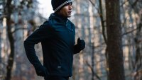 Fit man running through wooded area in winter