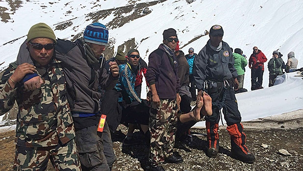 Rescue team members carry avalanche victims to safety at Thorong La pass area in Nepal, Friday, Oct. 17, 2014.