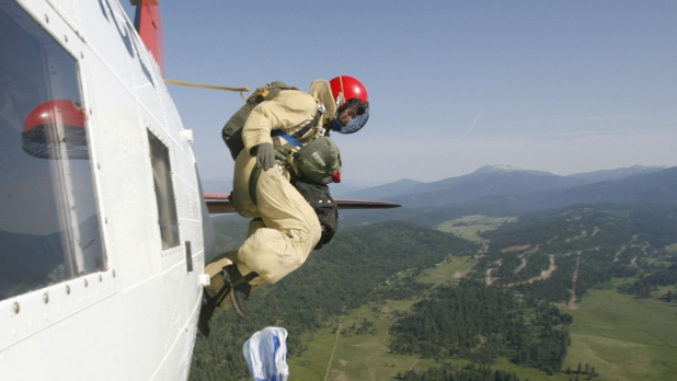 A smokejumper getting on top of an emerging fire.