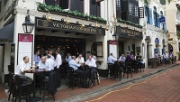 Drinkers enjoy a pint at a British style pub in Boat Quay, Singapore.