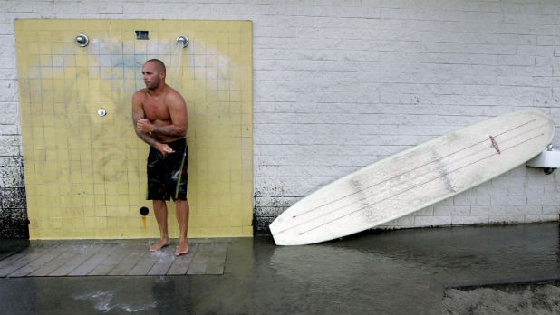 A surfer showers post-session at Malibu's Surfrider Beach, one of California's most polluted beaches after a rainfall.?