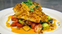 Zapp's and andouille-crusted redfish over garden vegetable hash with smoked tomato butter sauce and blackened shrimp.