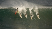 Six surfers drop into a wave during pre-contest surfing at the Eddie Aikau Big-Wave Invitational on December 8, 2009 in Waimea, Hawaii. The rare contest, which attracts big wave surfers from around the world, is held in memory of Hawaiian surf and lifeguard legend Eddie Aikau only when the waves are over 40 feet.