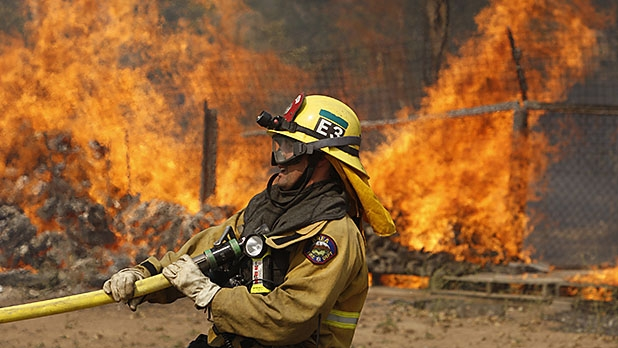 A firefighter pulls a hose in position while battling a wild fire on May 15, 2014 in San Marcos, California.