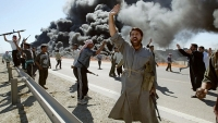 Iraqi Sunni Muslim insurgents celebrate in front of a burning US convoy they attacked April 8, 2004 in Abu Gharib, on the outskirts of the flashpoint town of Fallujah.