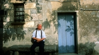 A Sardinian man sits in front of his house in the tiny village of San Salvatore.
