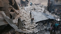 Civilians and rescue teams inspect the rubble of a destroyed building in Aleppo, the largest city in Syria.