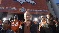 Denver Broncos Peyton Manning stands with DeMrcus Ware on stage as they look out over the crowd during the teams celebration. The Denver Broncos celebrated their Super Bowl victory with a a parade and celebration February 9, 2016 at the City & County Building.