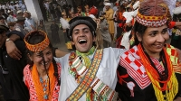 "A Kalash man laughs while dancing with women during the ""Joshi"" (spring) festival in the village of Batrik May 16, 2008 in the Kalasha Valleys, northwestern Pakistan."