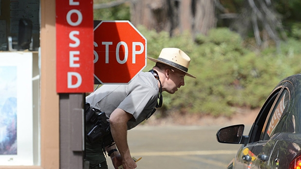 Park ranger Jeff Gardner informs visitors of the closure of Yosemite National Park due to the government shutdown Tuesday, October 1, 2013.