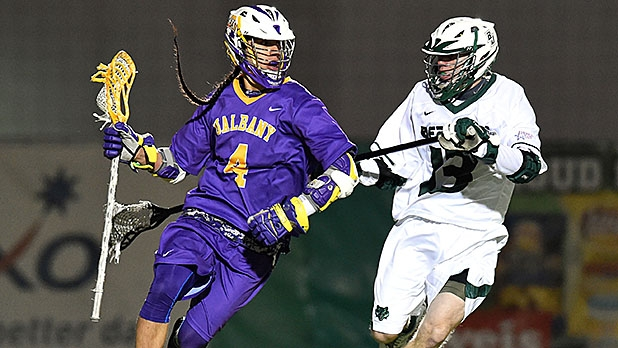 Albany attackman Lyle Thompson (left) dodges to the goal against the defense of the Binghamton Bearcats.