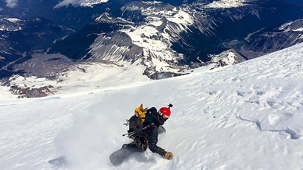 Abe Greenspan rides off the summit of Mount Rainier, the last of three volcanoes he accessed by bicycle with skier Brody Leven.