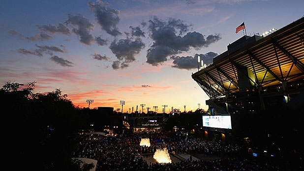 Fans watch play on a video screen in the south plaza outside of Arthur Ashe Stadium during sunset on Day Ten of the 2014 US Open at the USTA Billie Jean King National Tennis Center on September 3, 2014 in the Flushing neighborhood of the Queens borough of New York City.