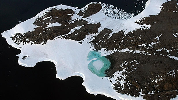 A turquoise lake forms from melting snow near Cape Folger on the Budd Coast in the Australian Antarctic Territory.